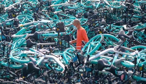"""郑州一停车场内,万余辆""""老款""""共享单车被堆成小山"""