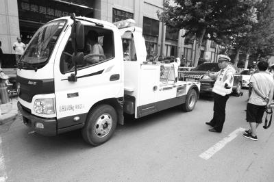 一辆拖车将违停车辆拖移.jpg