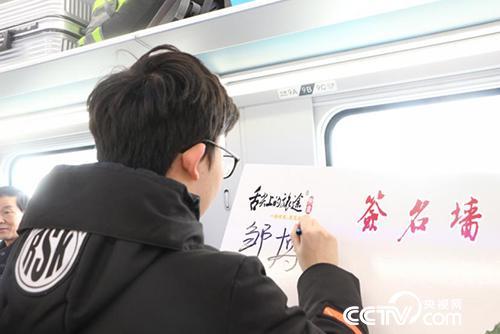 乘客邹博在签名墙上留念。