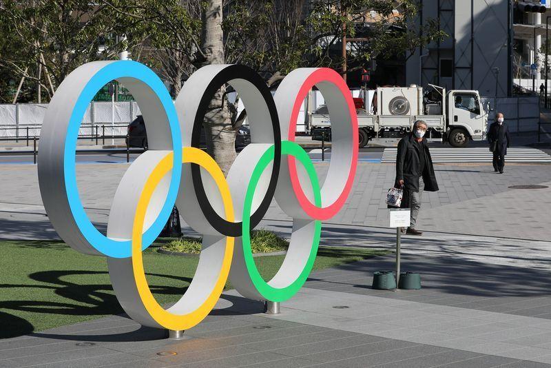 3月12日,在日本东京,行人戴着口罩经过2020年东京奥运会主体育场附近的五环标志。.jpg?x-oss-process=style/w10